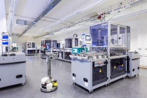 Die Dresdner IIot-Modellfabrik richtet sich an Unternehmen unterschiedlicher Branchen, die Digitalisierungs- und IoT-Lösungen einführen möchten. Die technische Ausstattung besteht aus drei in die Anlage integrierte Roboterzellen, einer CNC-Zelle, einem Hochregallager, eine Vielzahl von technischen Modulen um typische Anwendungsfälle wie Drucken, Prüfen oder Pressen nachzubilden, einem Handarbeitsplatz, einer Cobot-Station, mehreren FTS und einer flexibel einsetzbaren Roboterzelle. – Bild: HTW Dresden, Peter Sebb